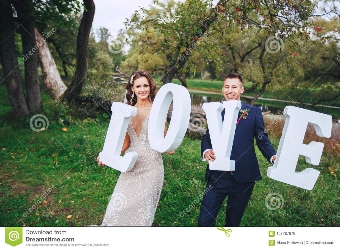 happy wedding couple holding big white love letters