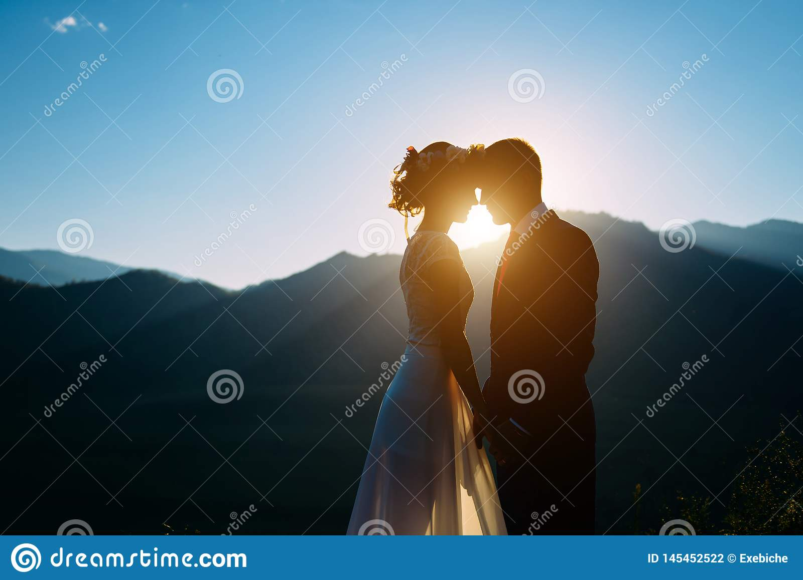 Happy wedding couple staying and kissing over the beautiful landscape with mountains
