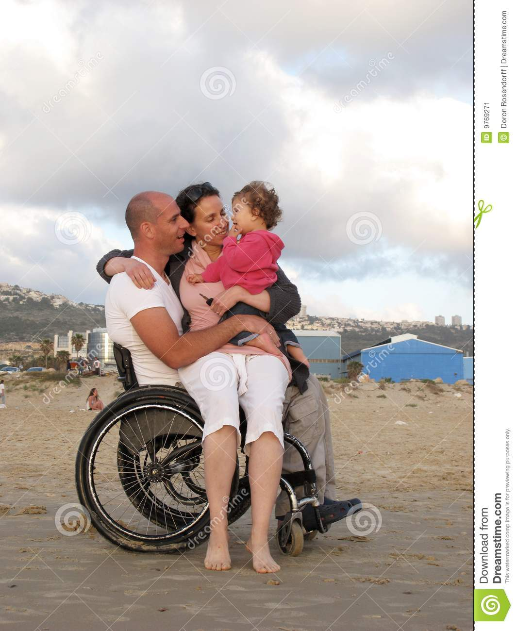 Family Enjoying Time Together On Beautiful Foggy Beach: Happy Wheelchair Family Stock Image