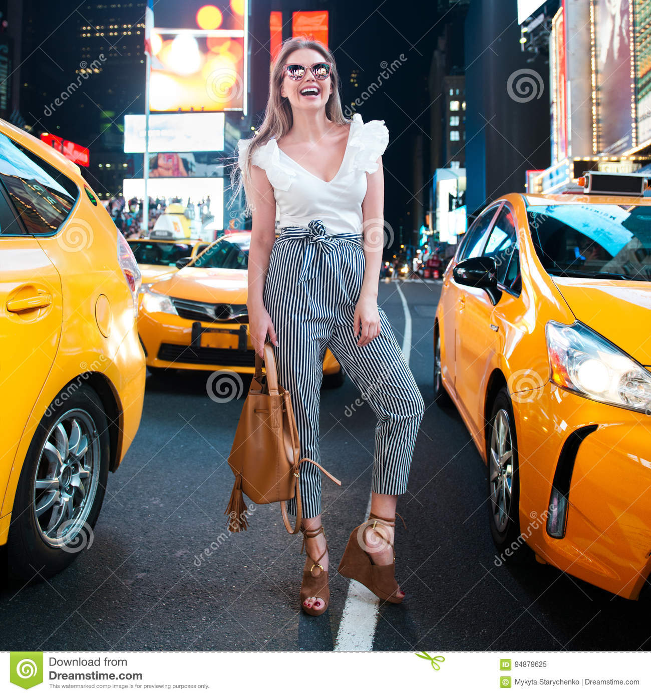 Happy woman with a bag in night New York City Times Square street enjoy the summer vacation and smiling with yellow taxi around.