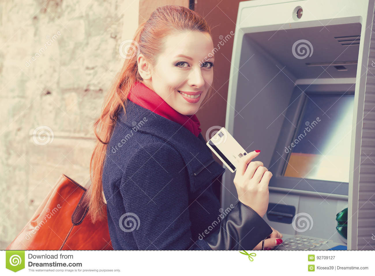 Happy woman with bank card using ATM