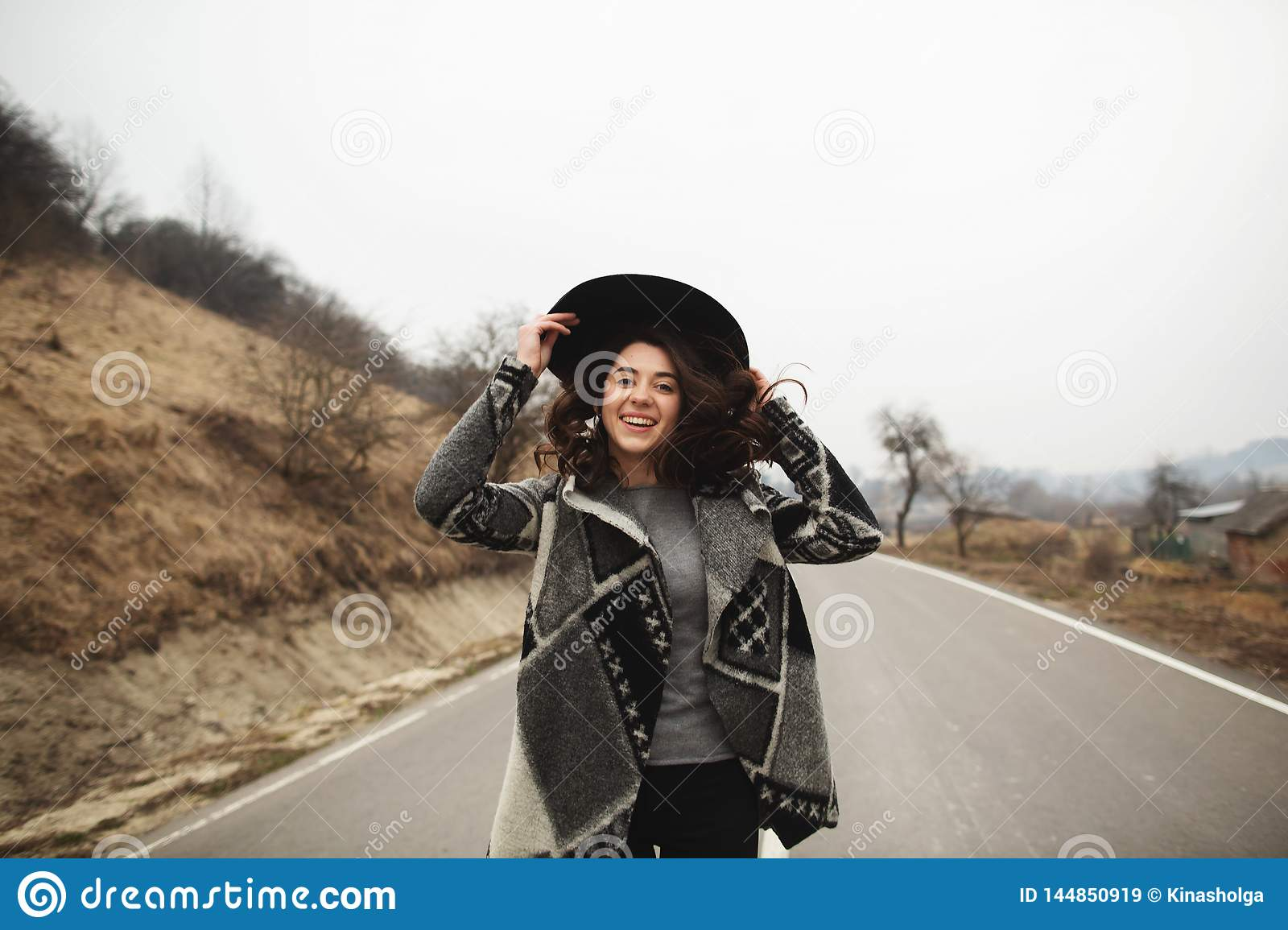 Happy woman in a beautiful gray cardigan and black hat rides along the way