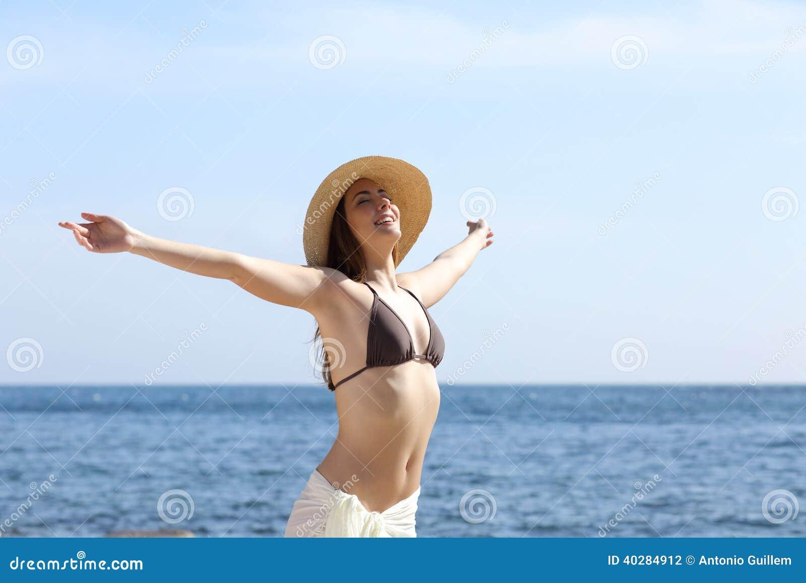 Happy Woman Breathing Fresh Air On The Beach Raising Arms
