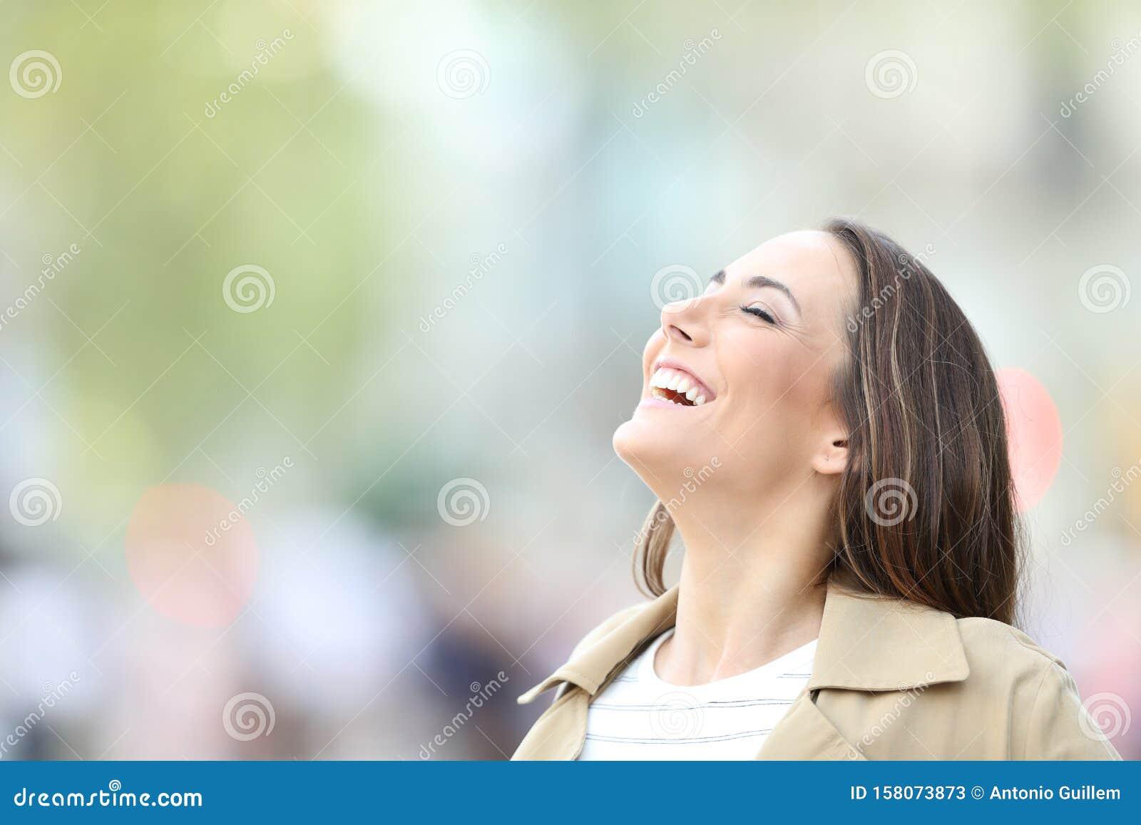 Happy woman breathing fresh air in the street