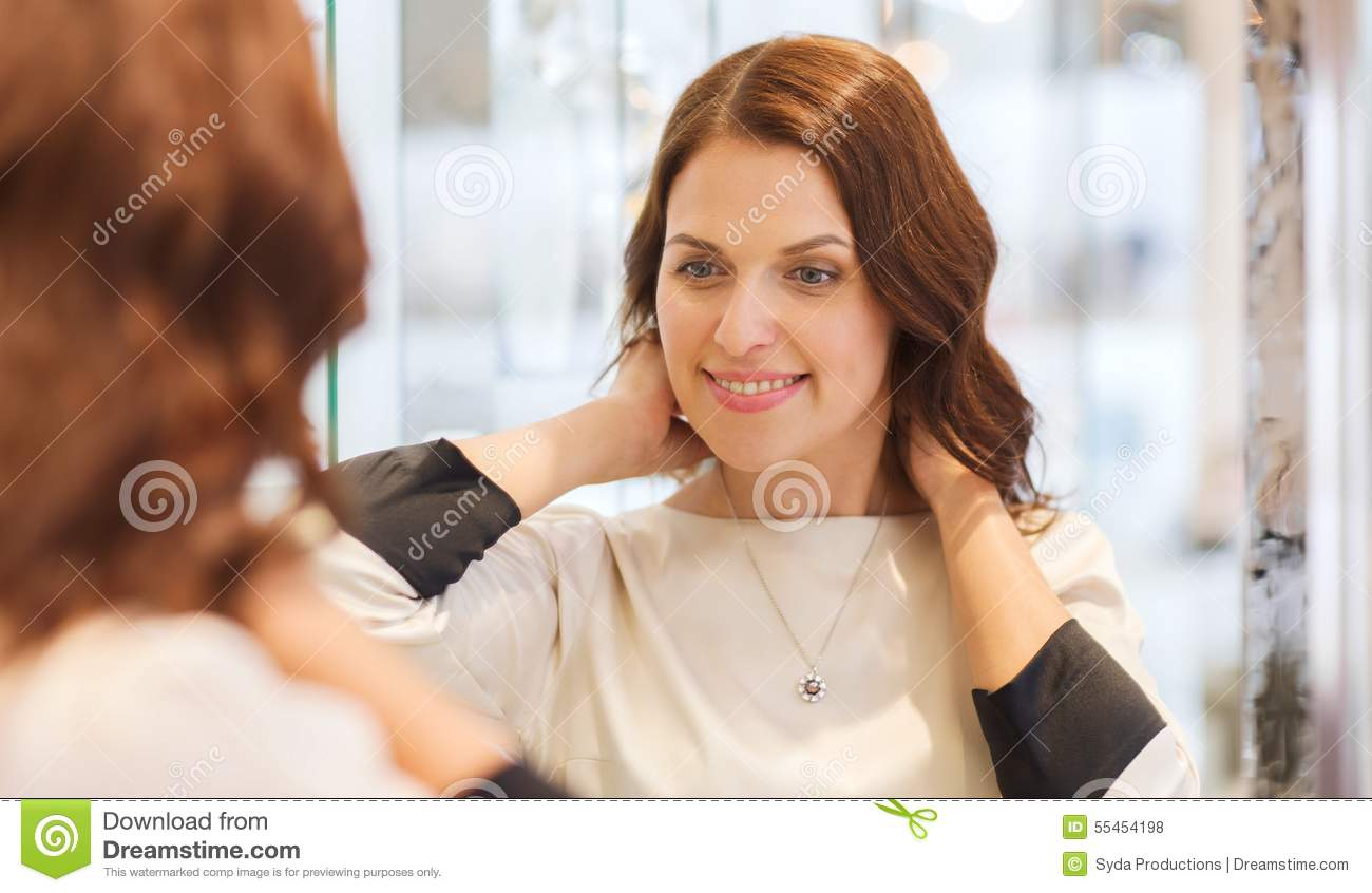Happy woman choosing pendant at jewelry store stock photo for Jewelry sale online shopping