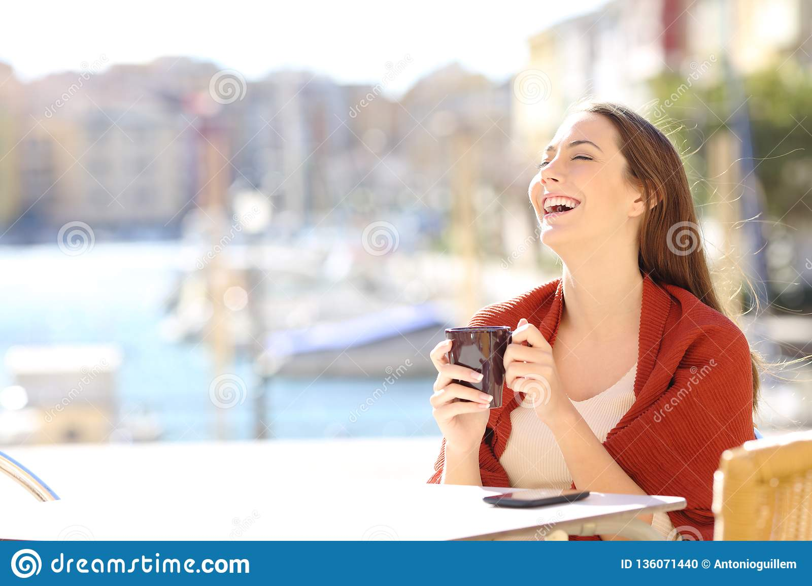 Happy woman in a coffee shop enjoying free time