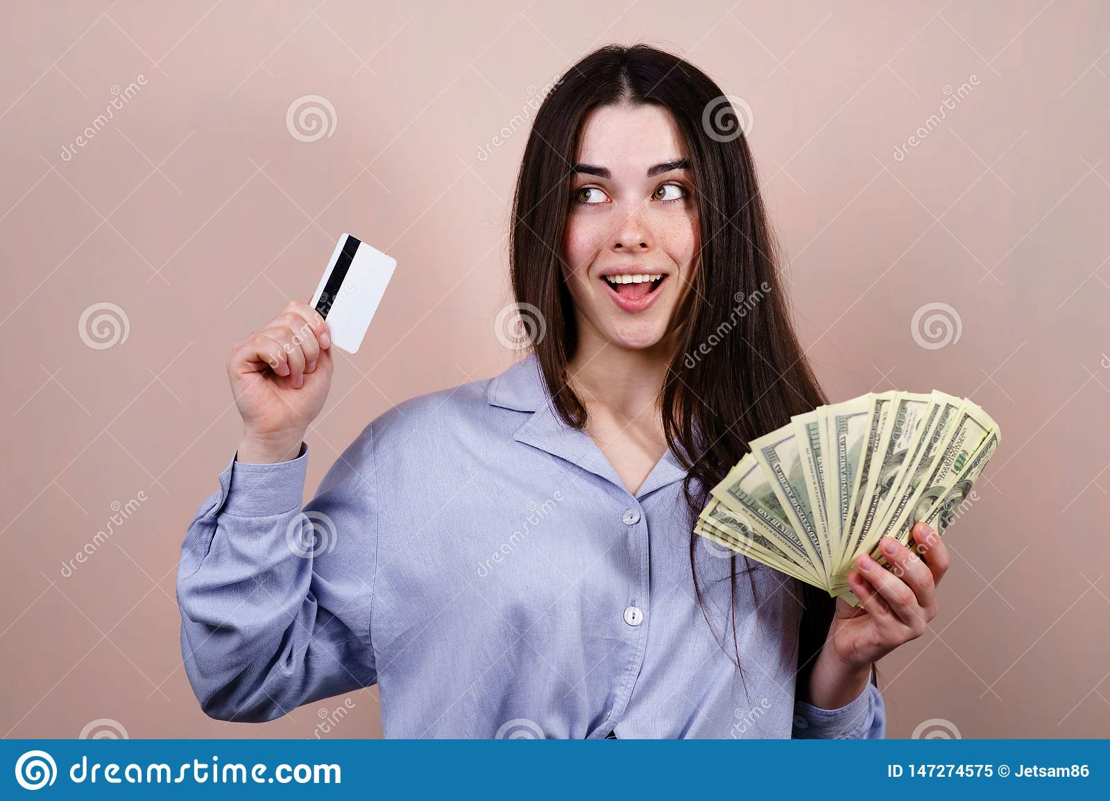 Happy woman with credit card and dollar bills