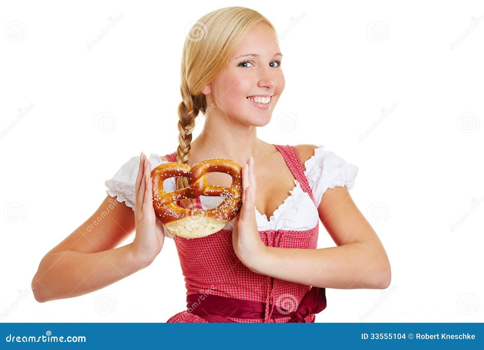 Happy woman in dirndl with pretzel