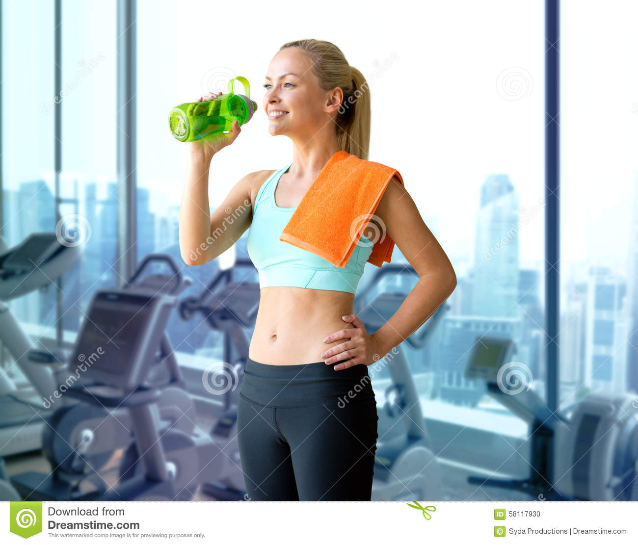 Happy woman drinking water from bottle in gym stock photo image happy woman drinking water from bottle in gym sciox Choice Image