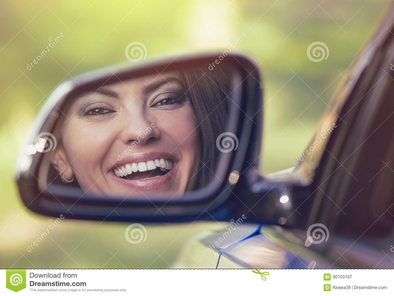 Happy Woman Driver Looking In Car Side View Mirror