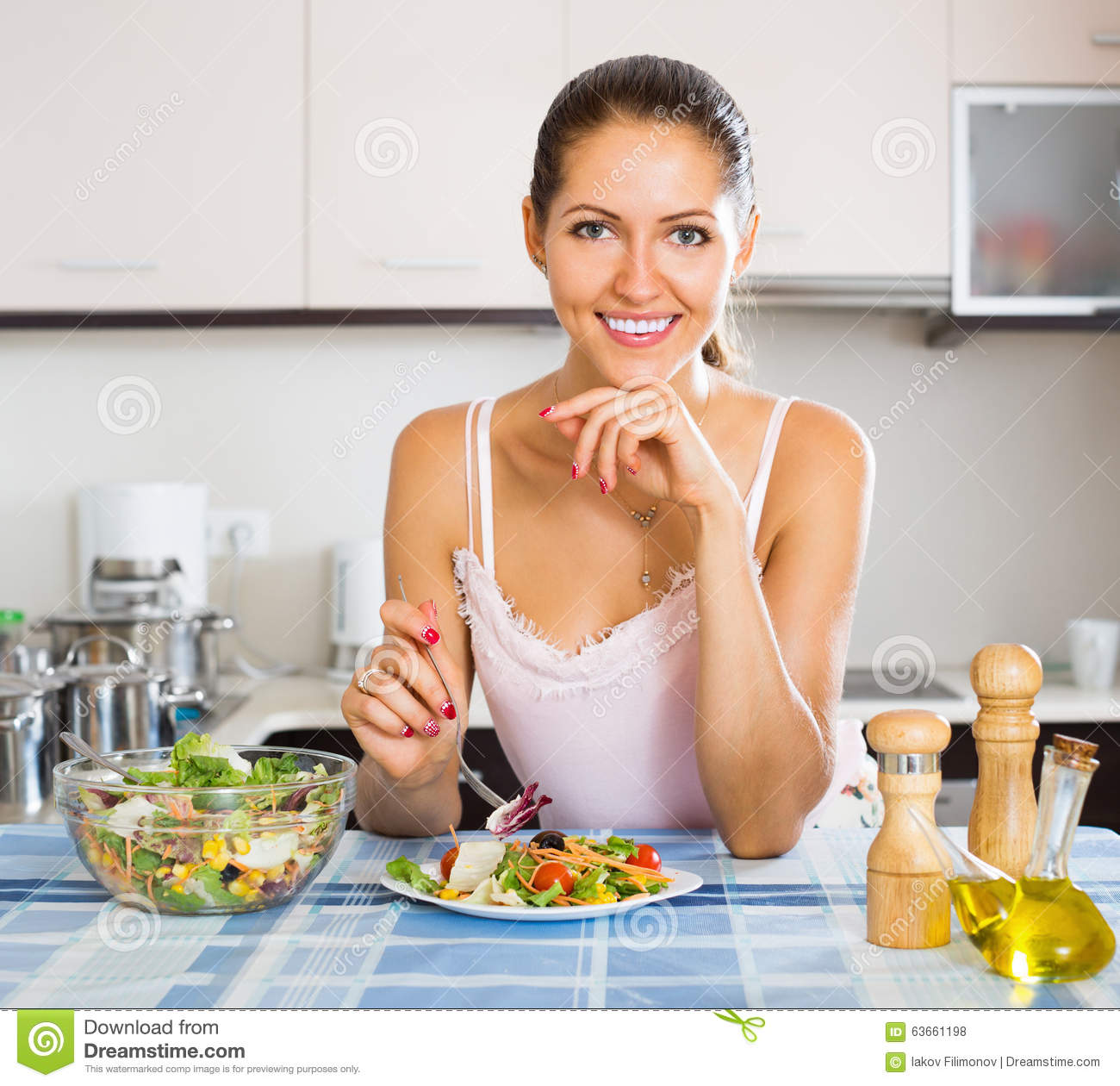 Happy woman eating at kitchen table stock photo image for Eating table