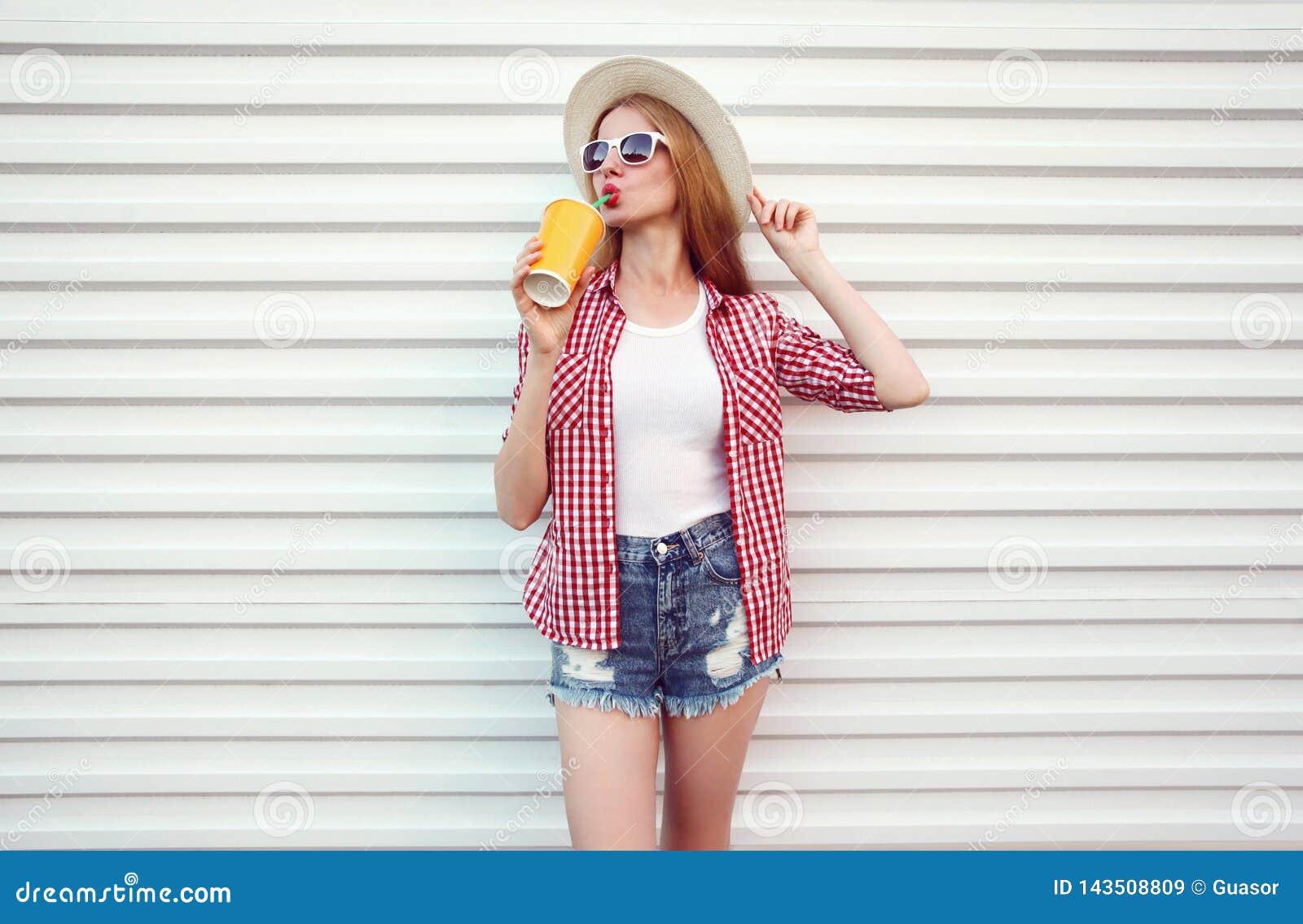 Happy woman enjoying fresh orange juice in summer round straw hat, checkered shirt, shorts on white wall