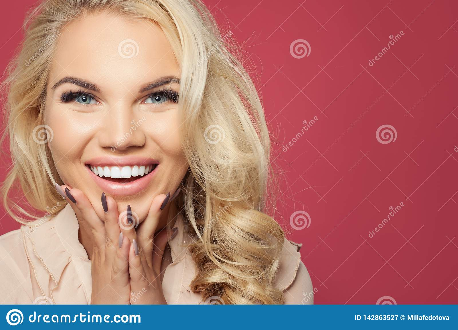 Happy woman face closeup portrait. Laughing girl on pink background, pretty face