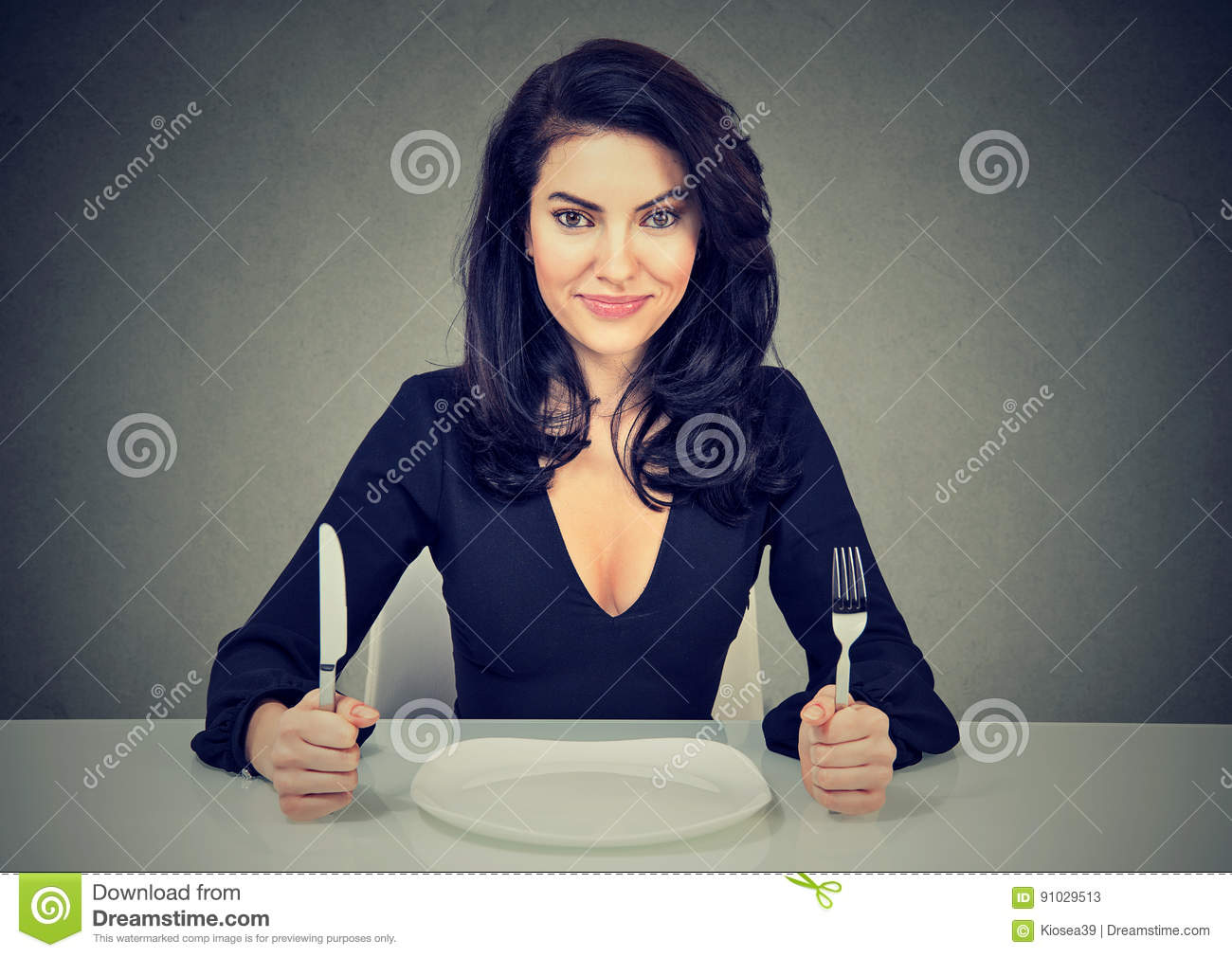 Happy woman with fork and knife sitting at table with empty plate