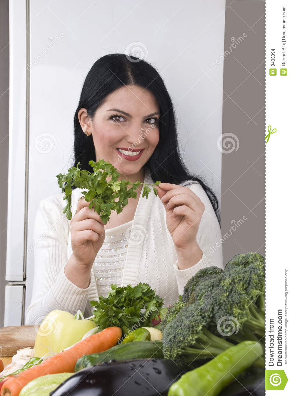 Happy woman with fresh parsley and vegetables