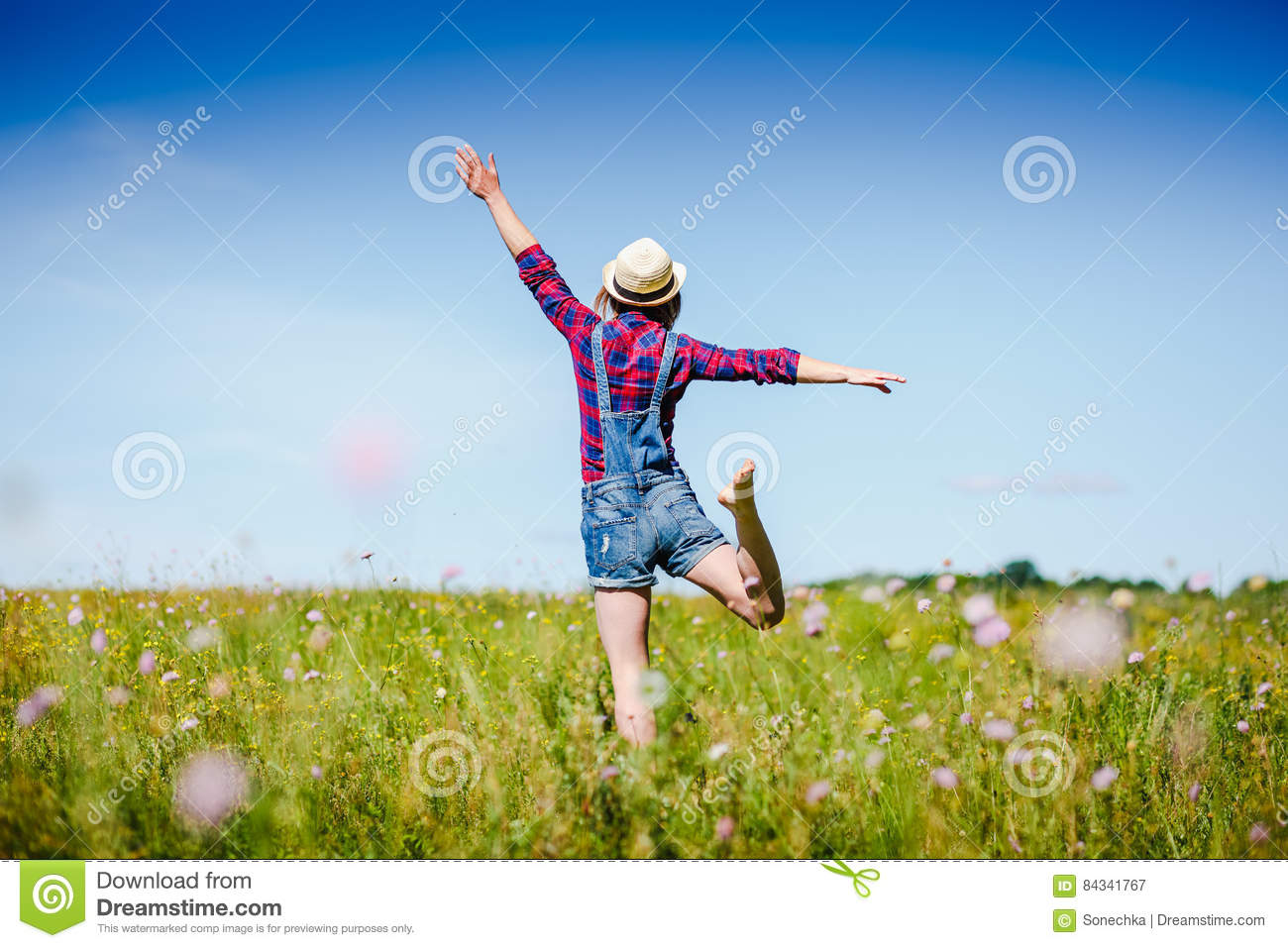 Happy woman in hat jumping in green field against blue sky