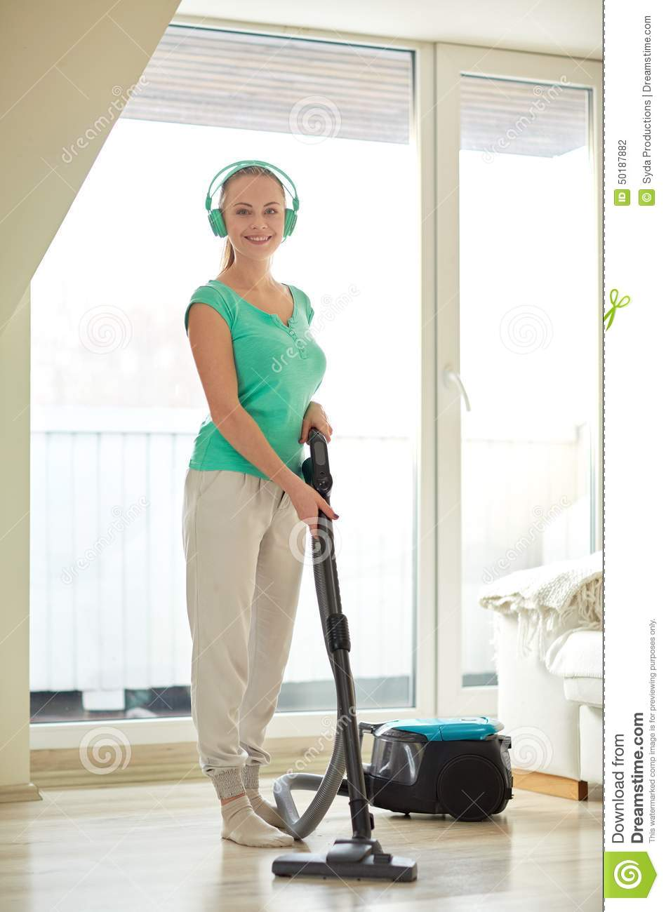 Happy Woman In Headphones With Vacuum Cleaner Stock Photo
