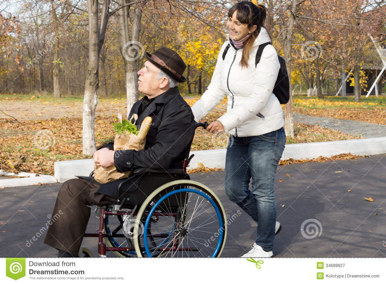 Happy Woman Helping A Disabled Elderly Man Royalty Free