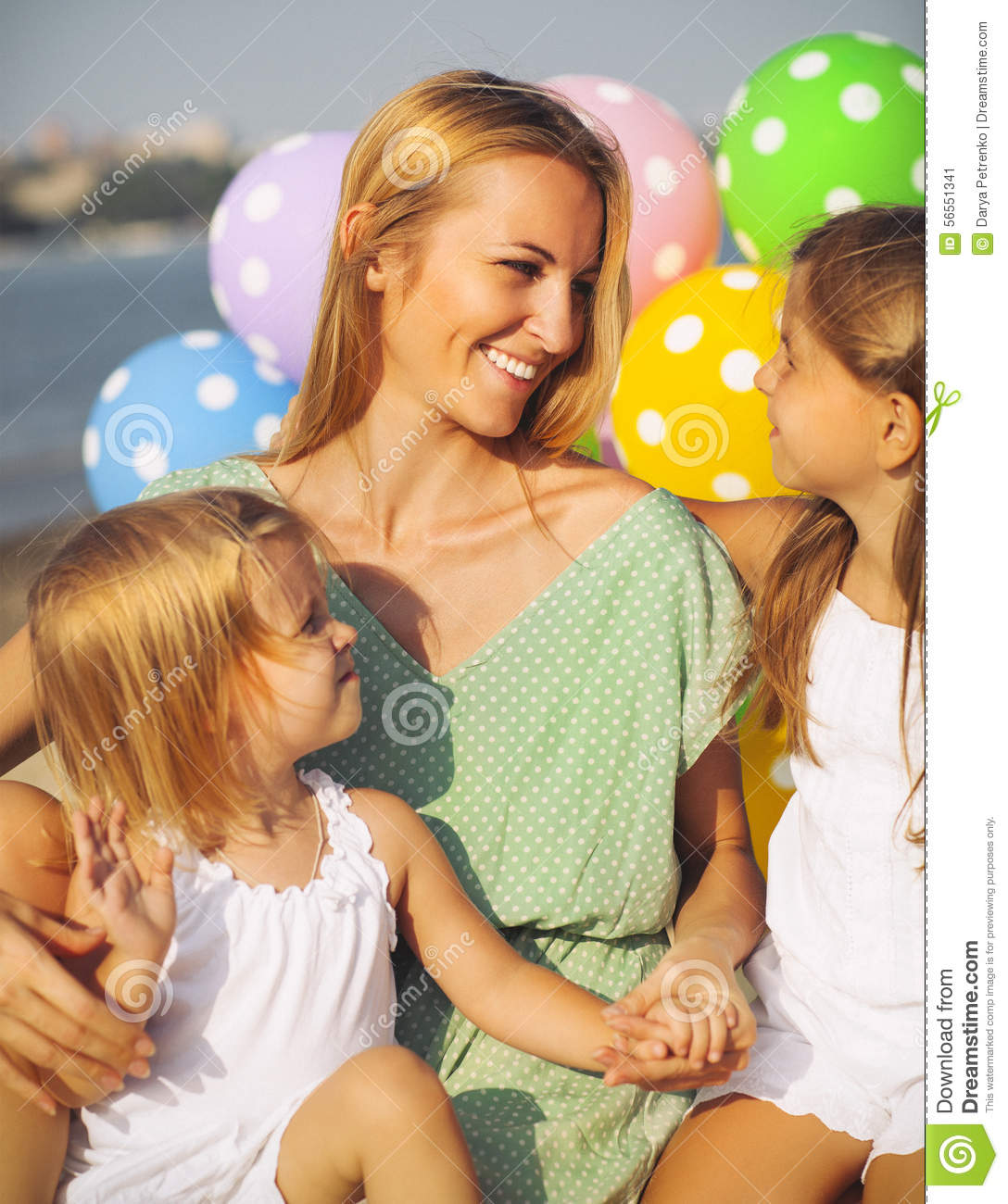 Happy woman and her little daughters at the beach with ballons