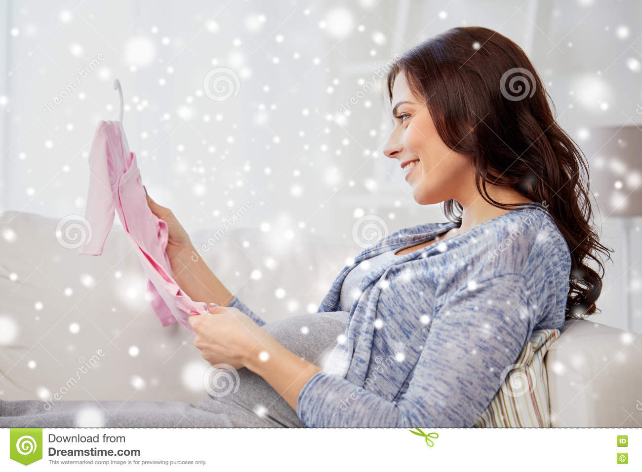 b420f07d2454e Motherhood, pregnancy, people, winter and kids clothing concept - happy  woman holding and looking at pink baby girls bodysuit at home over snow