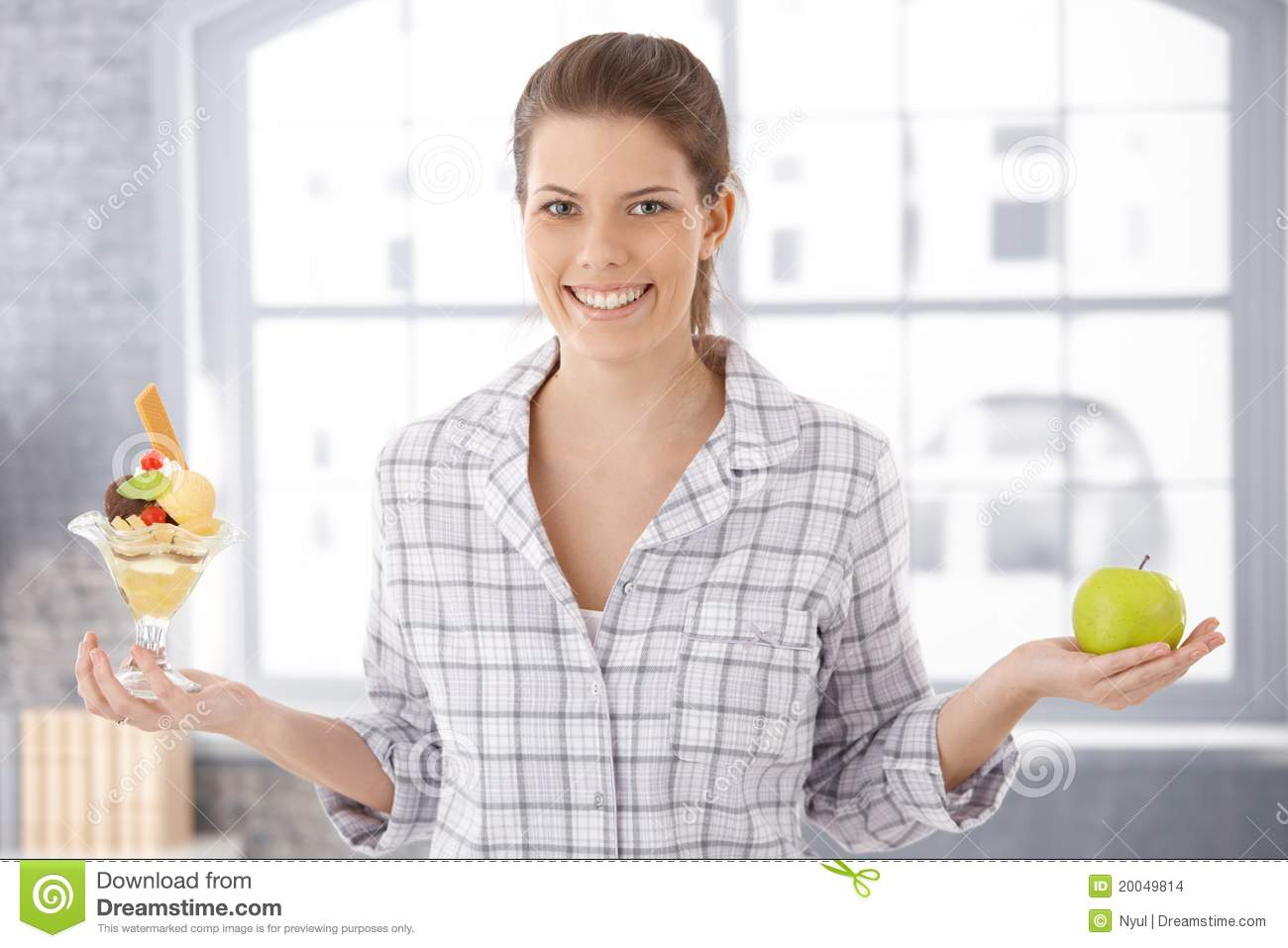 Happy woman holding icecream cup and apple