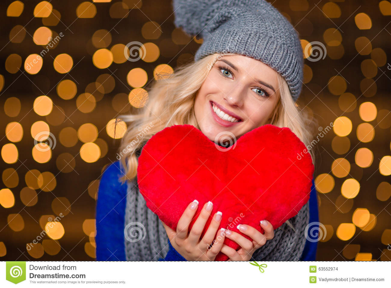 Happy woman holding red heart over holidays lights background