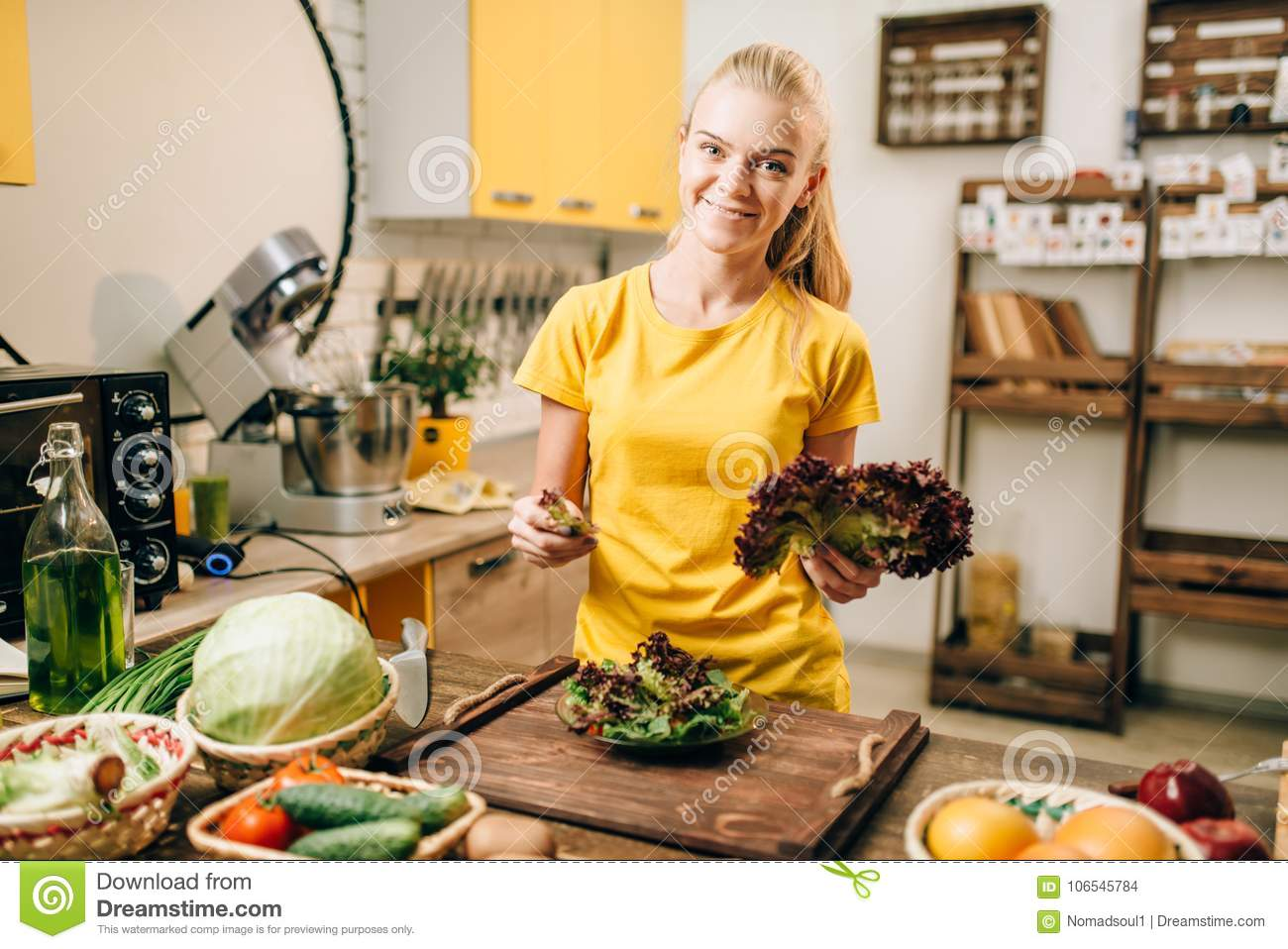 Happy woman holding salad, cooking healthy food