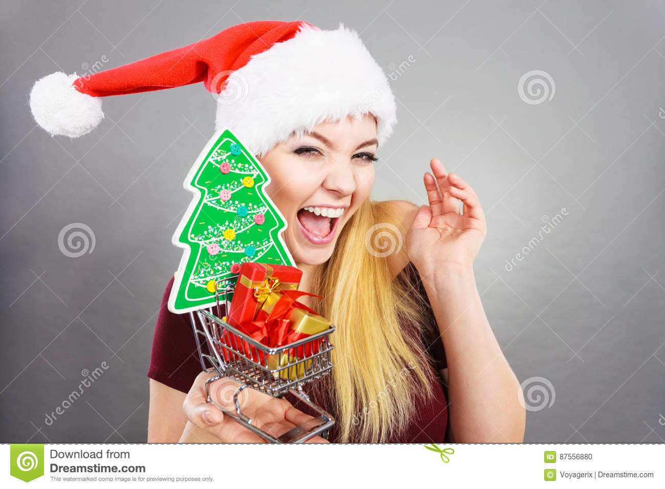 Happy woman holding shopping cart with christmas gifts