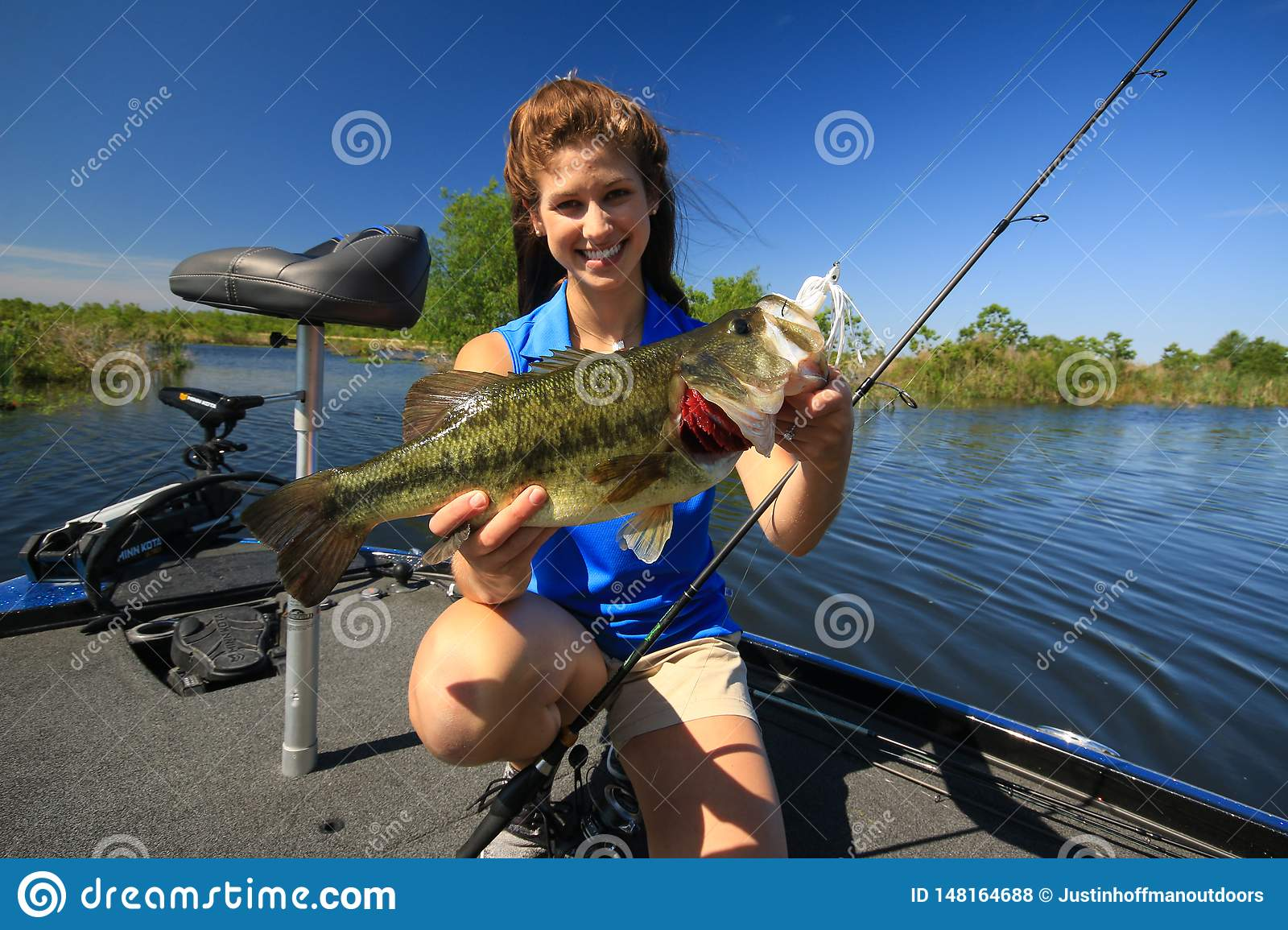 Woman Holding Large Mouth Bass Caught Fishing From Boat