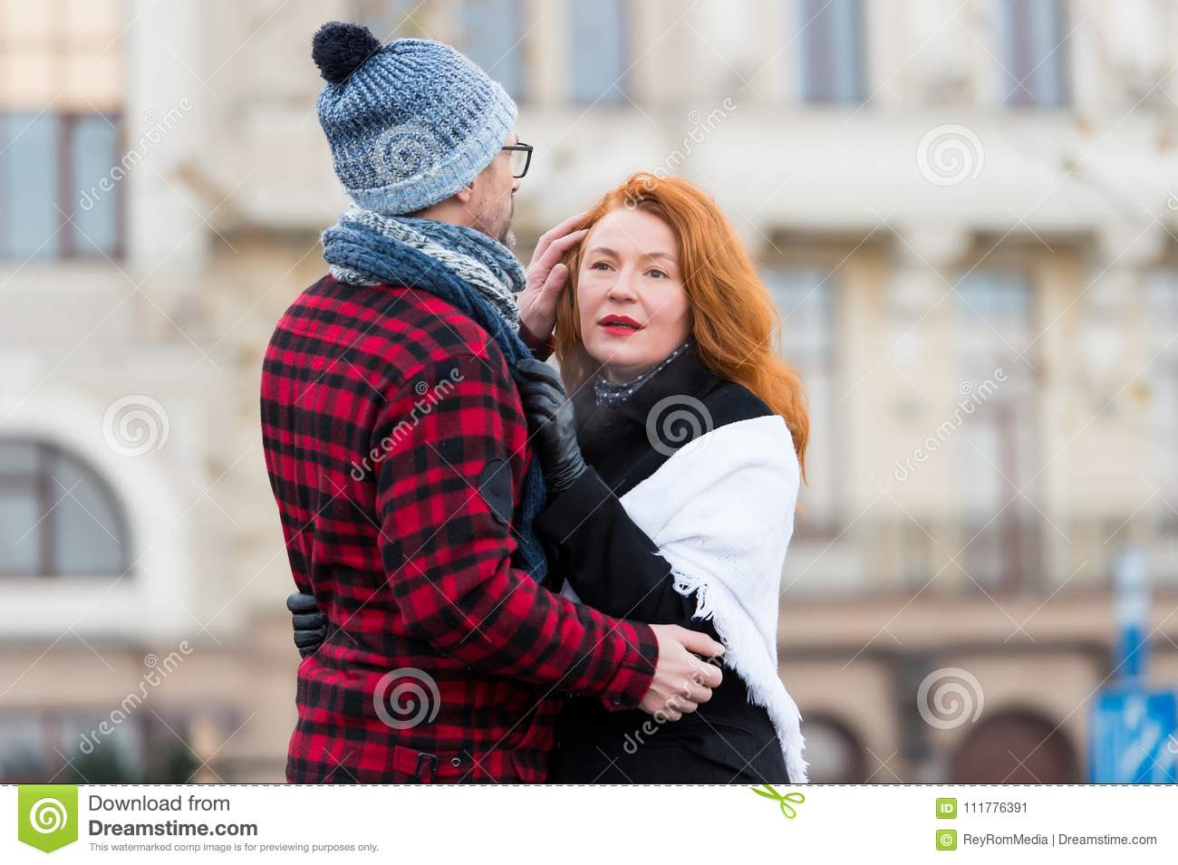 Happy woman hugs man in hat on the street. Happy couple hugging on the city background. Sensual brunette woman