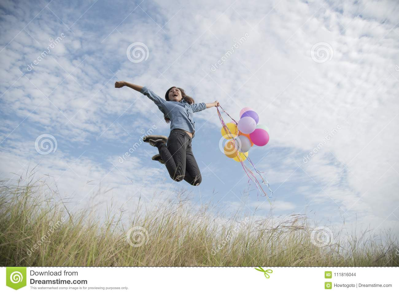 Happy woman jumping with air balloons on the meadow