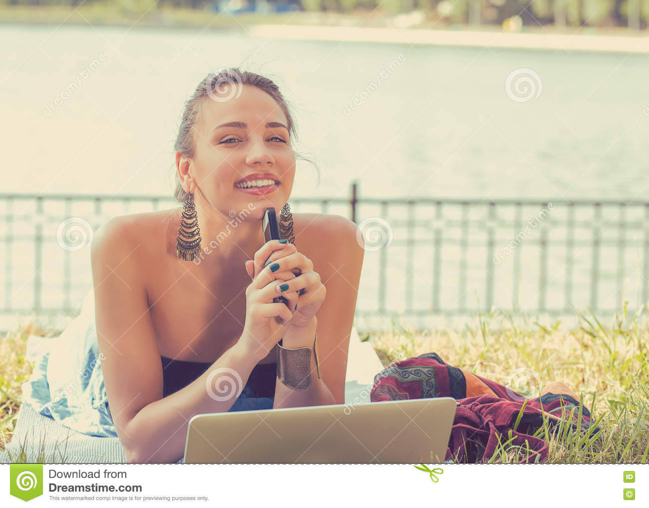Happy woman with laptop computer and mobile phone relaxing in a park