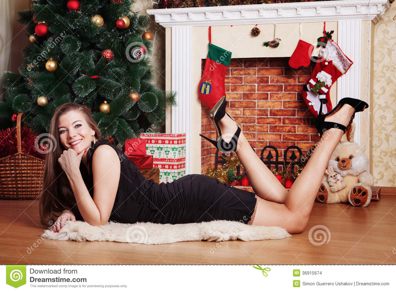 Happy Woman Laying On The Floor In Front Of Christmas Tree