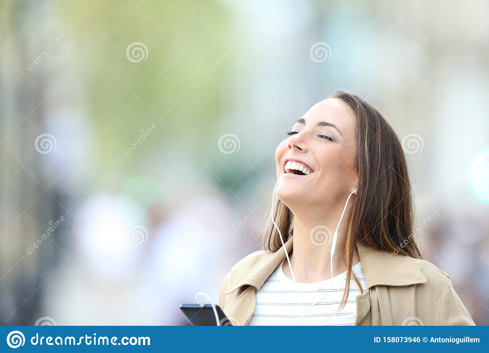 Happy woman listening to music breathing in the street