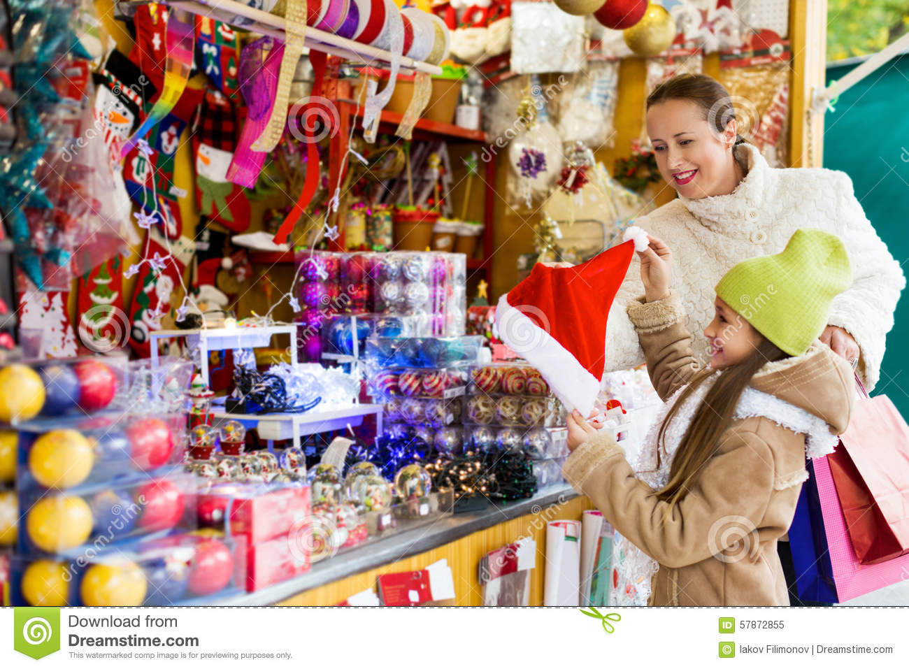 Happy Woman With Little Daughter Buying Gifts At Christmas