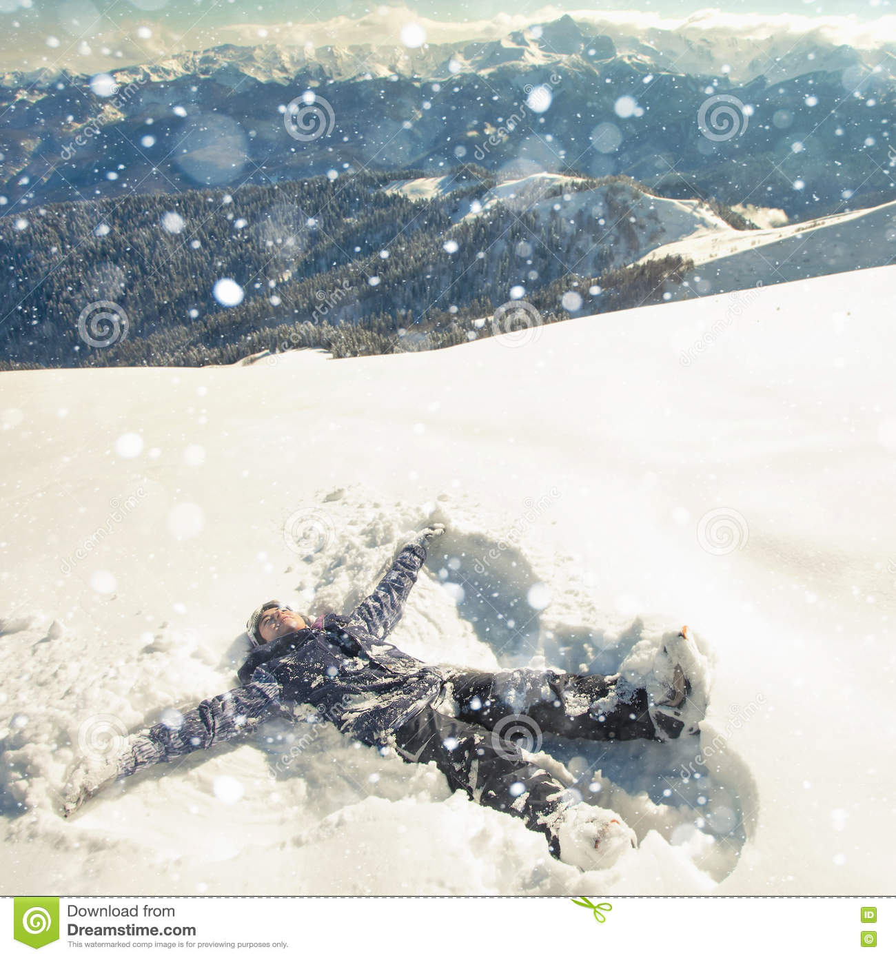 Happy woman making snow angel in the mountain ski