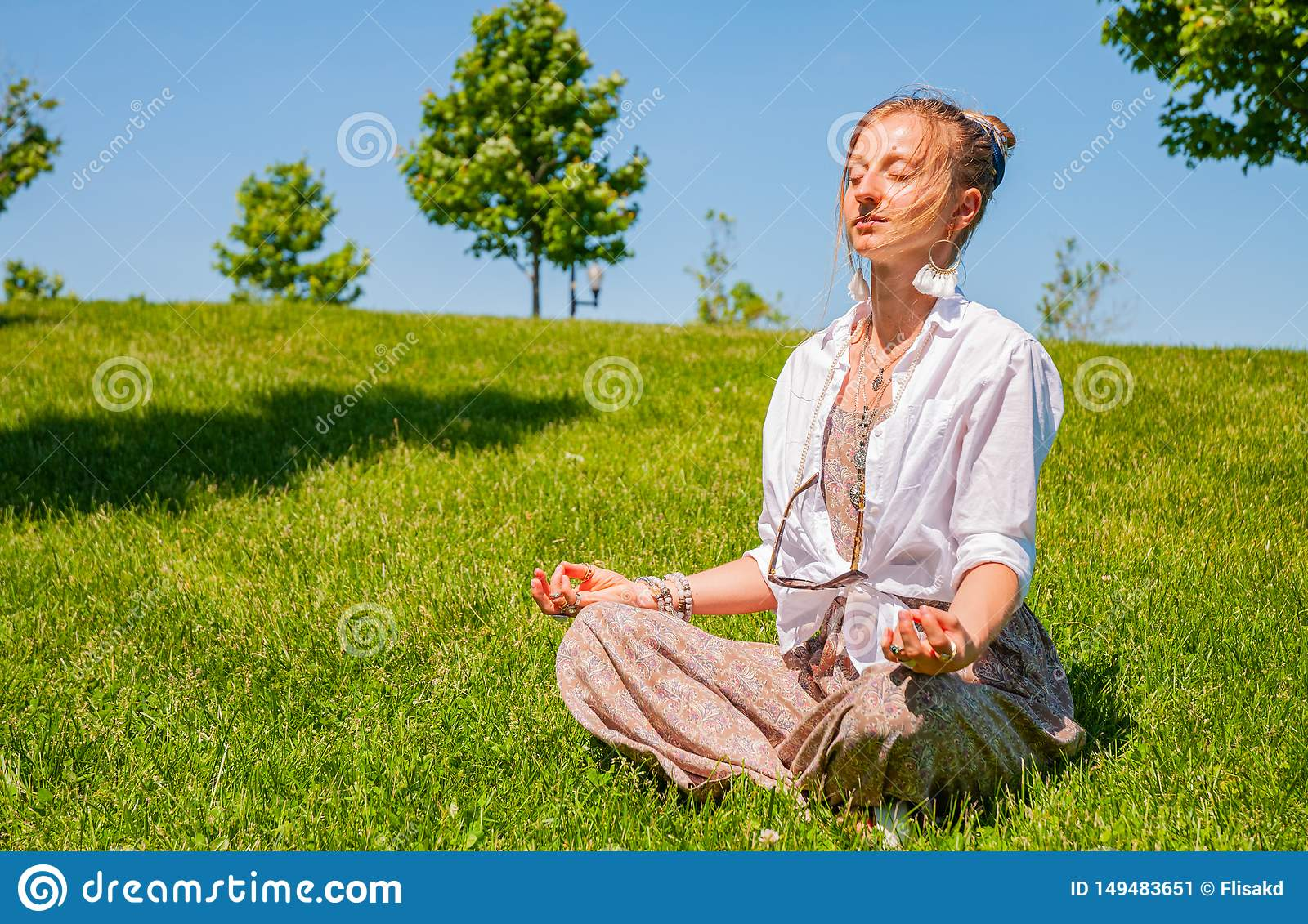 Happy woman is meditating sitting in Lotus pose on grass lawn. Beautiful boho style woman with accessories enjoy summer sunny day