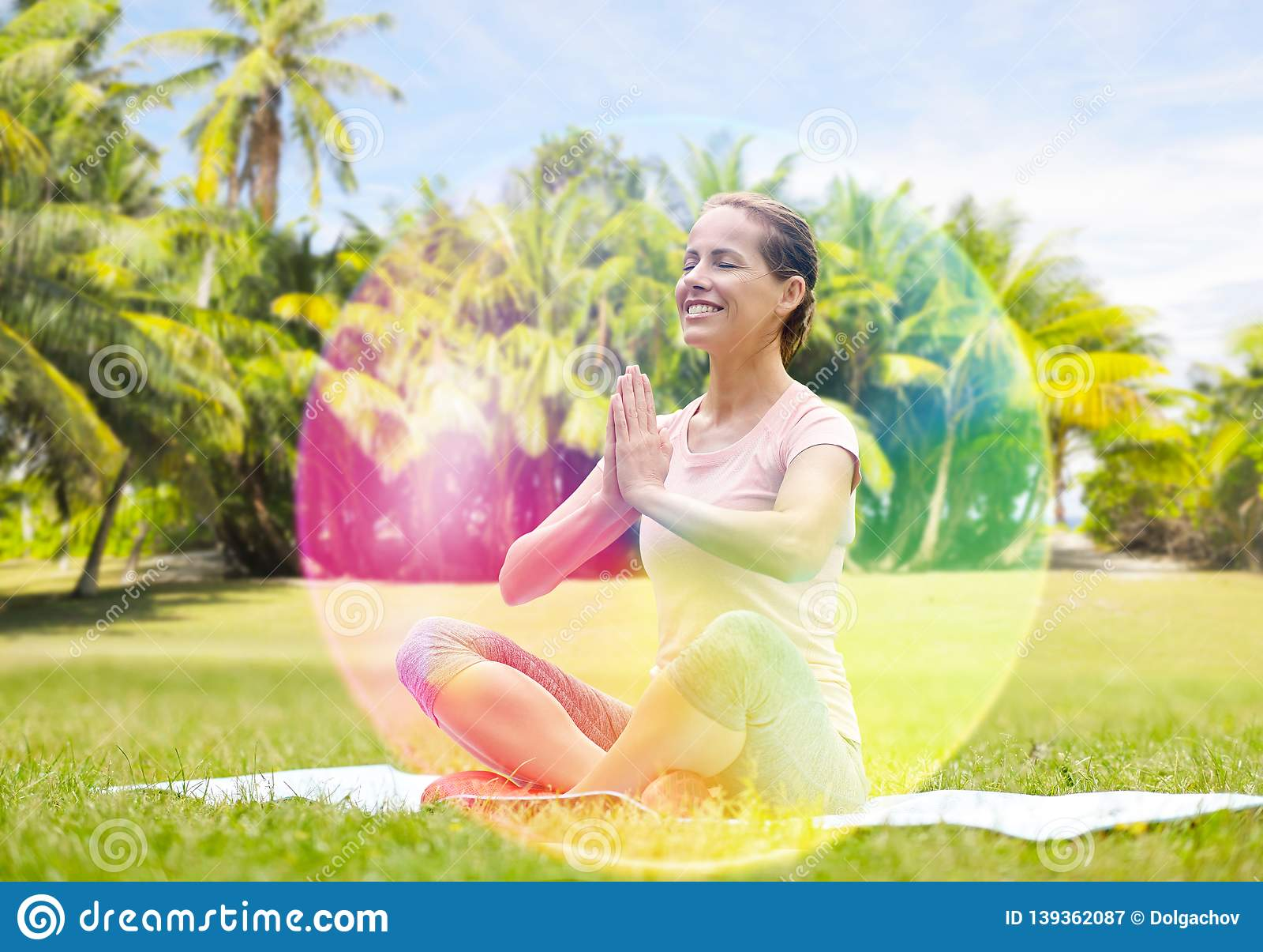 Happy woman meditating in summer park over aura