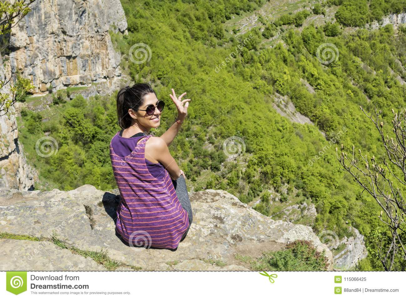 Happy Woman Sitting on the Edge of Rock in the Summer Mountain