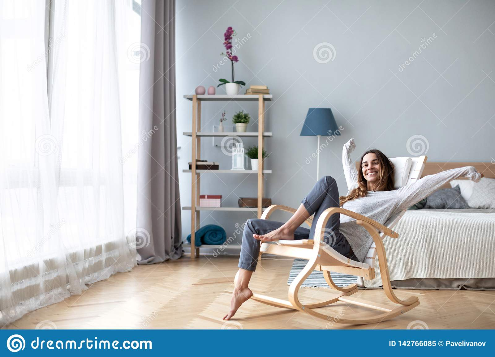 Happy woman resting comfortably sitting on modern chair in the living room at home