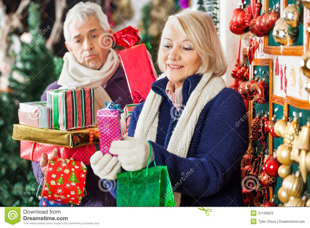 Senior Christmas Gifts: Happy Woman Shopping Presents With Tired Man Stock Image