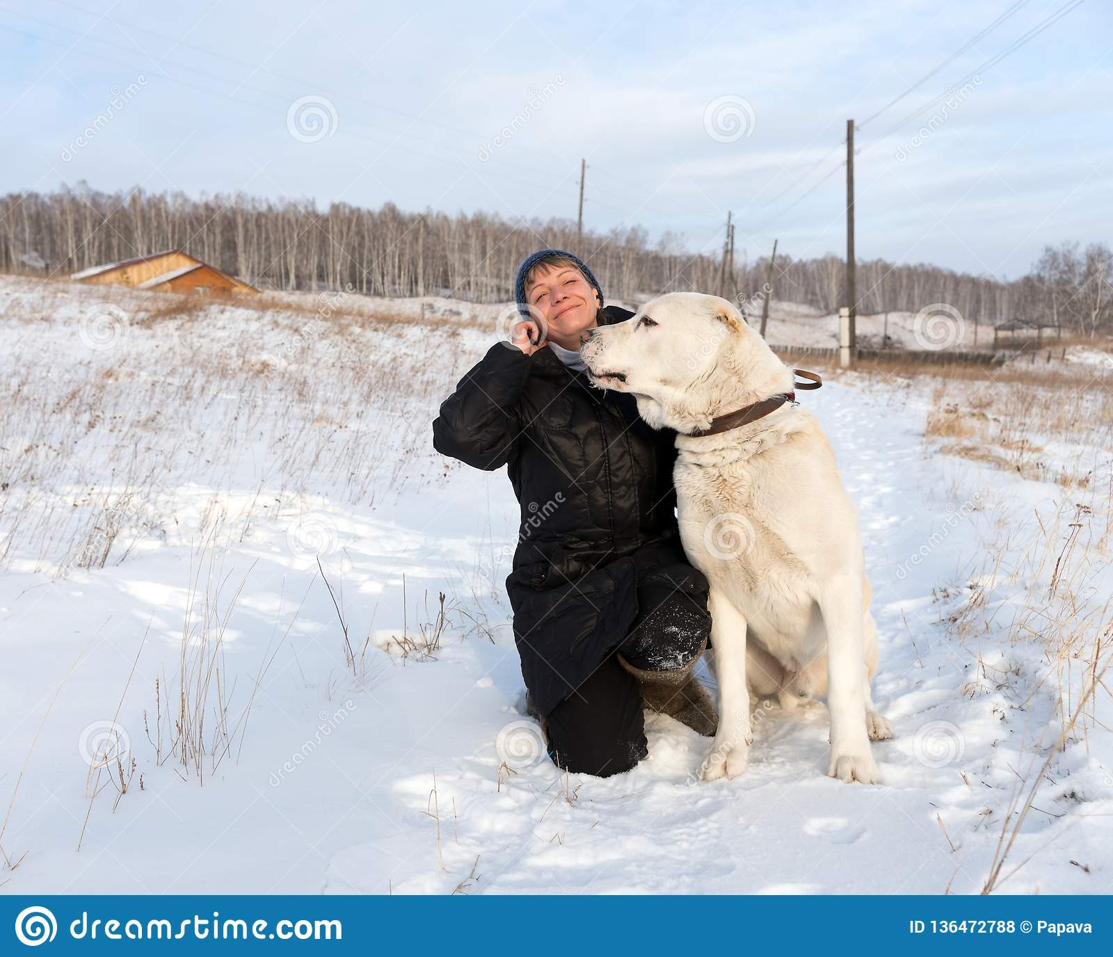 Happy woman is sitting with a Central Asian Shepherd on a winter rural road against the backdrop of the village