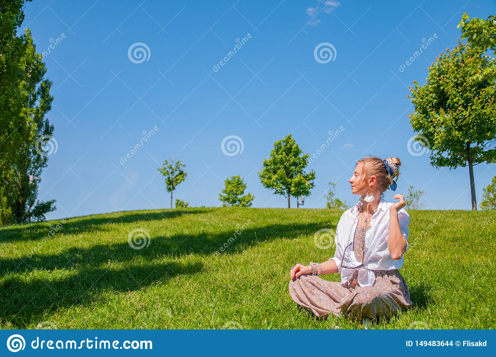 Happy woman is sitting on grass lawn. Beautiful boho style woman with accessories enjoy summer sunny day in park