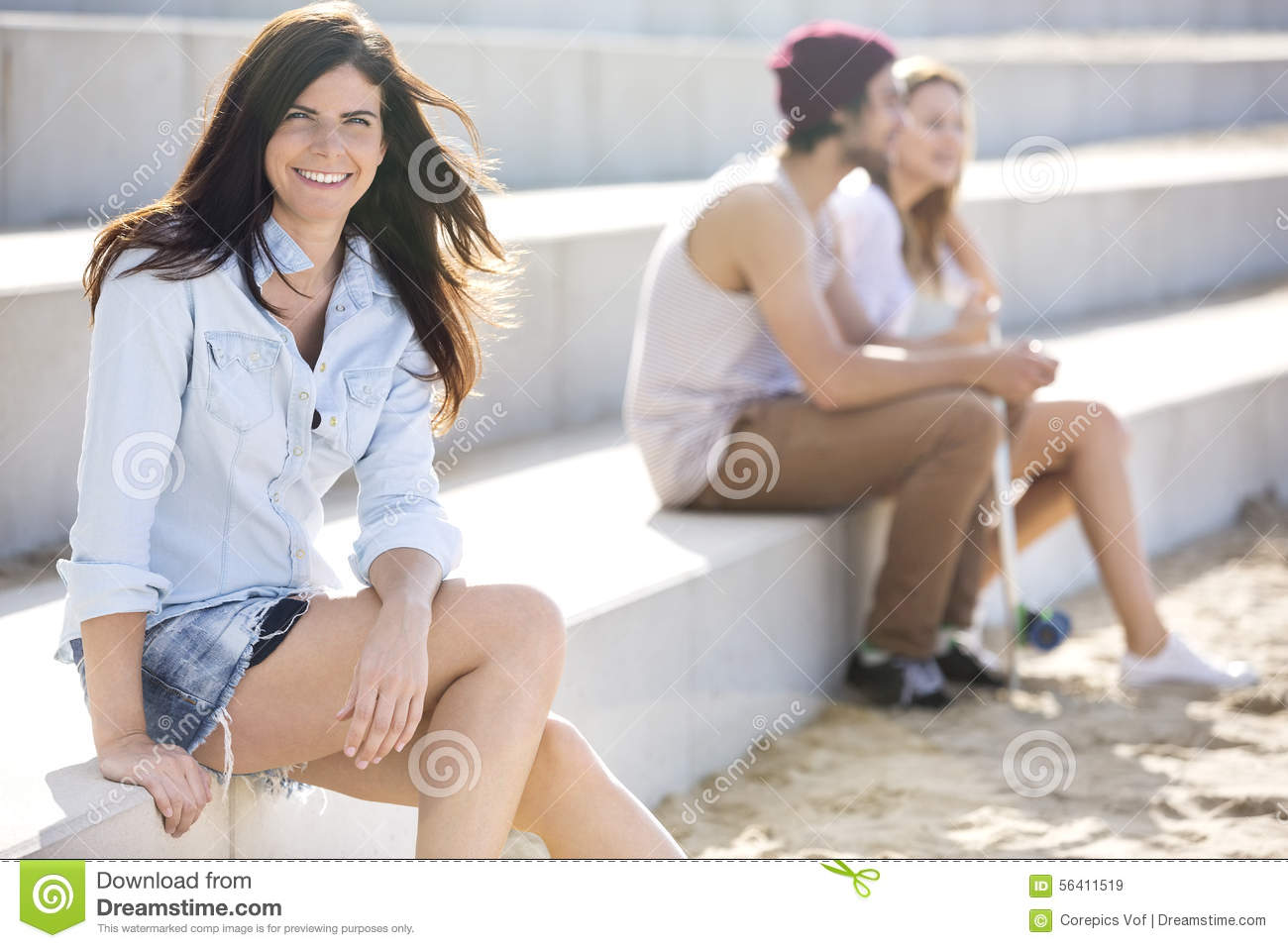 Happy Woman Sitting On Steps At Beach