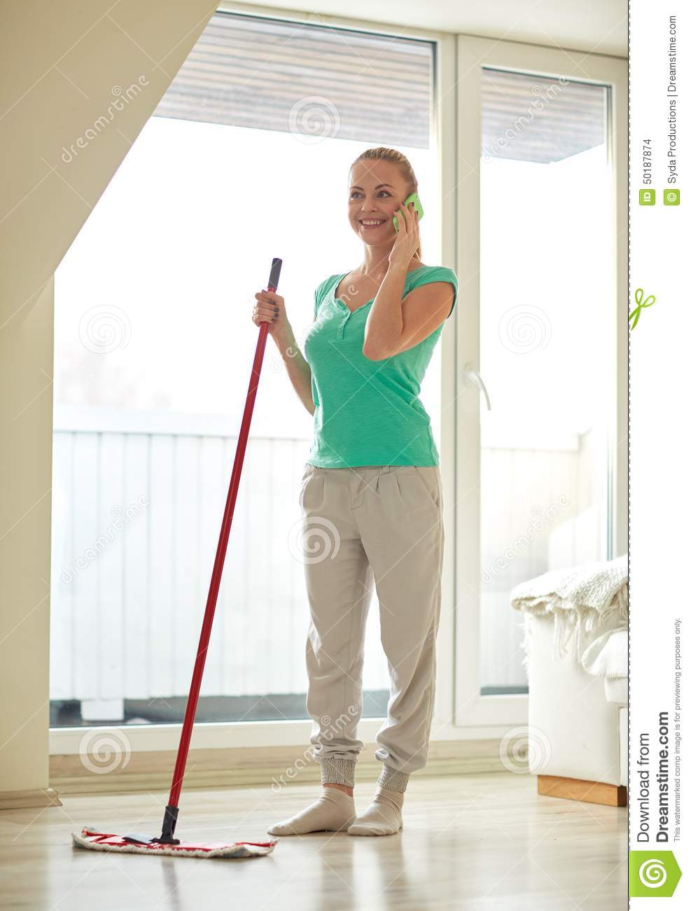 Happy woman with smartphone mopping floor at home stock for Floor someone
