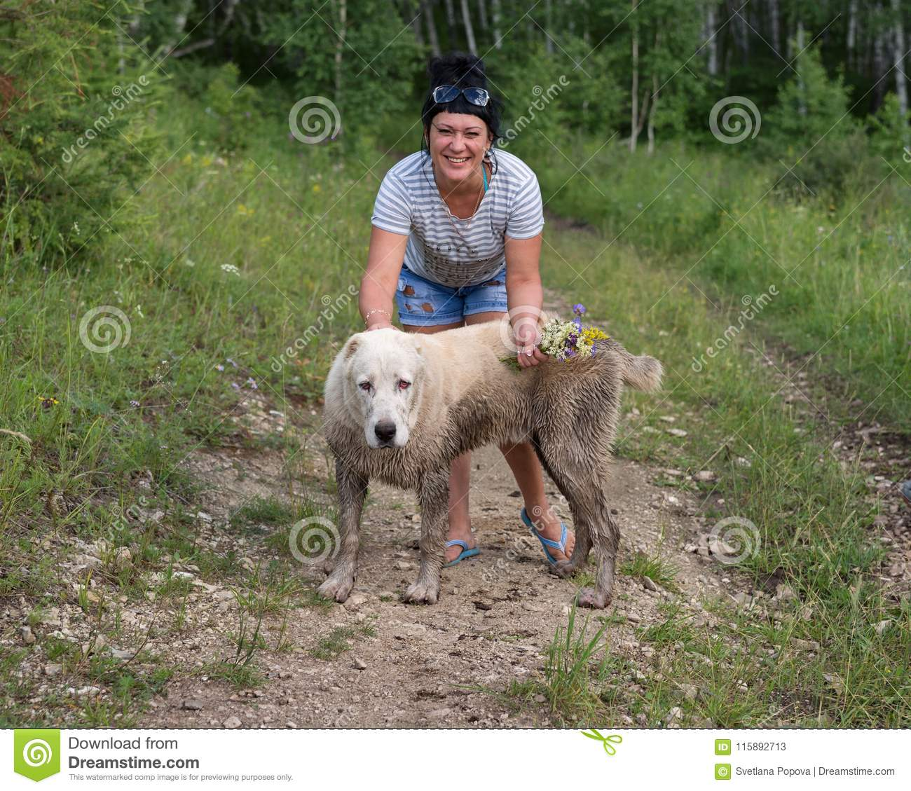 Happy woman standing with grimy dog in the woods.