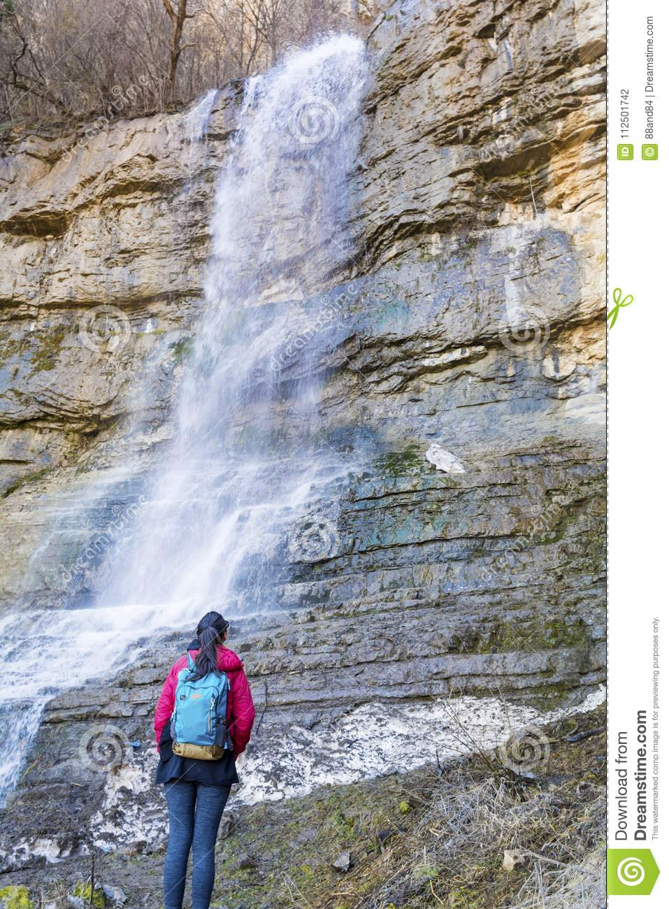 Hiker Woman Looking a Big Waterfall in the Rocks