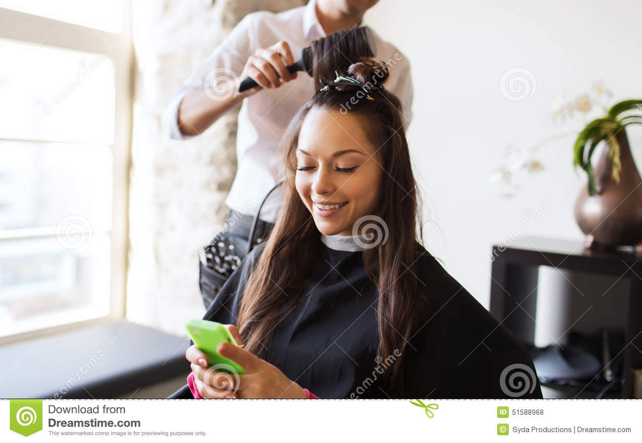 Happy woman with stylist making hairdo at salon stock for Photo salon