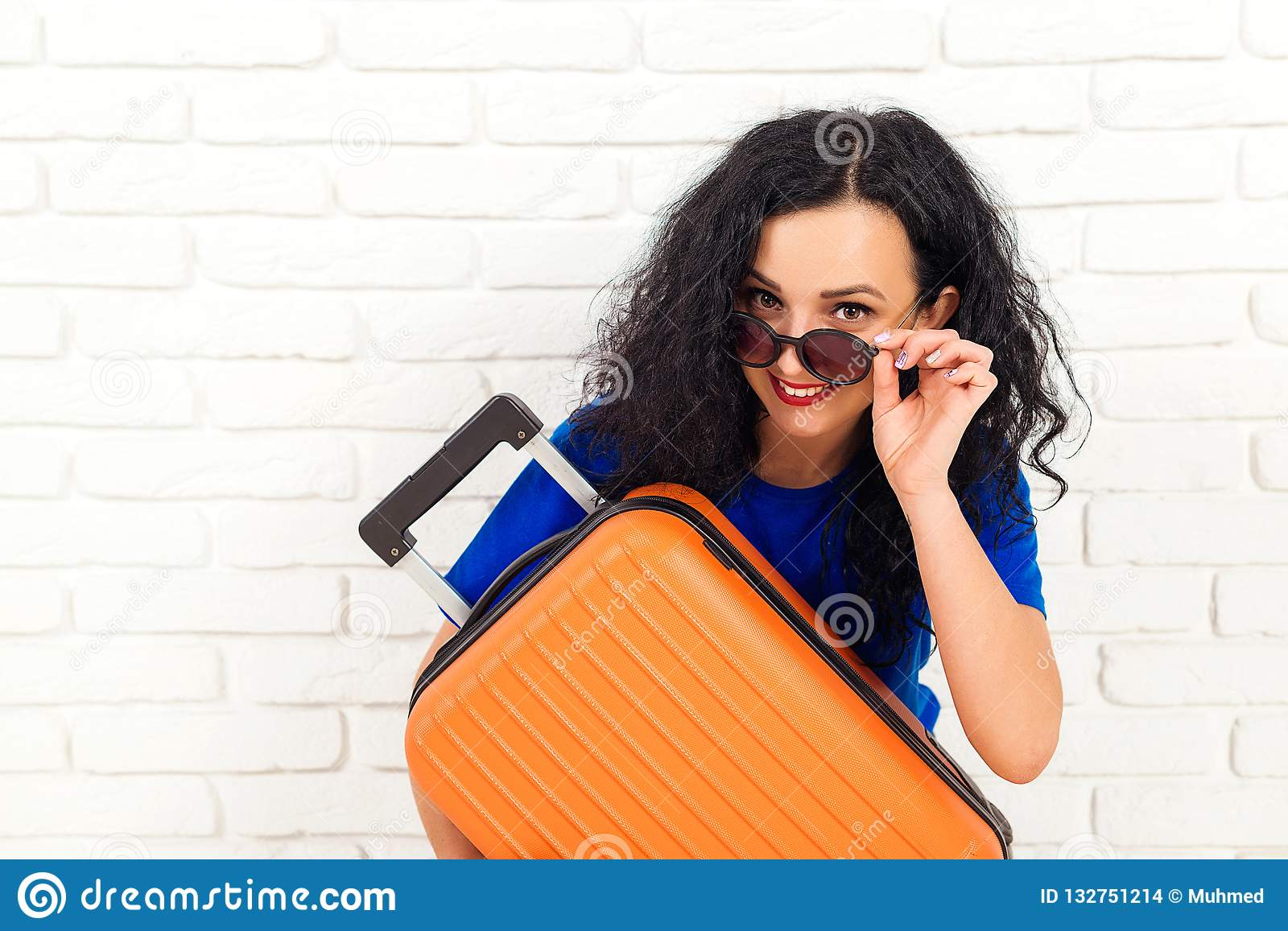 Happy woman in sunglasses holding travel suitcase. Emotional girl before trip isolated on white brick wall. Lifestyle, travel and