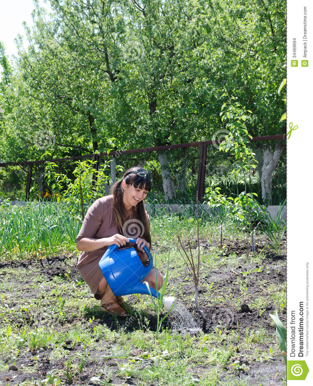 Happy Woman Tending To Her Vegetable Garden Stock Images